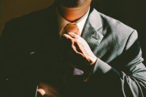 Image of man in business suit adjusting neck tie
