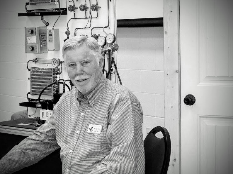 Greyscale image of Nelson Davis sitting in office, with a display of gauges and air conditioning parts in the background