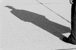 Greyscale image of shadow on sidewalk of person dressed in graduation cap and gown